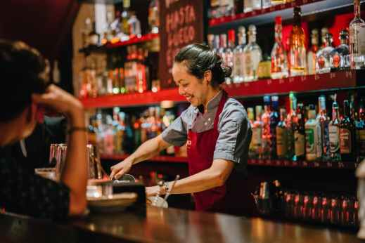 woman bartender smiling while mixing liqueurs