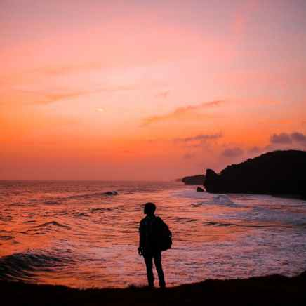 silhouette photo of man with backpack standing in seashore during golden hour